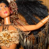 """Adira is spendid and strong with her proud look, and wild hair caught up on each side big and her wid hair caught up on each side. She wears a tassel belt and black skirt, which is accented by a gold breast plate blouse. She looks like a tribal warrior and her beautiful armband of """"feathers""""."""