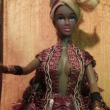 """""""Samra"""" is indeed a """"Dark Skinned"""" beauty. She wears attire of an earthy colored fringed gown, gold edged belt, front and back skirt anels, gold arm bands, and a traditiona stye head wrap fit for a queen. ."""