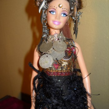Tribal Diva Doll, Nalia is adorned and embellished with hair coiled and coifed, a jingly silver headdress and tribal coin necklace.  Her ethnic choli blouse is almost backless, she has a fringy beaded belly dance belt and flashy deep gold dance pants,  Her face bears tribal markings and she wears wrist gauntlets.